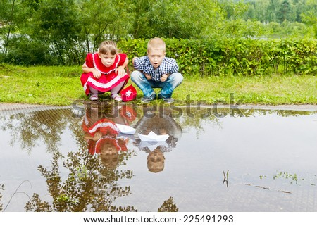 adorable little sister and brother playing with paper boats - stock photo