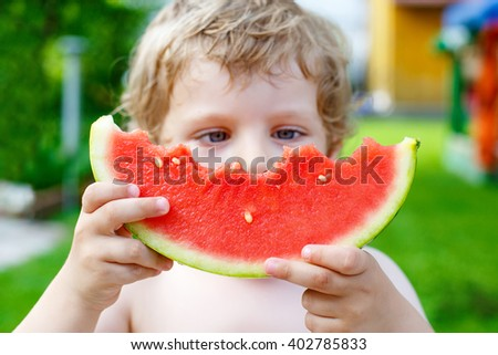 Adorable little toddler boy with blond hairs eating watermelon in summer garden. Kid tasting healthy snack. Selective focus on watermelon - stock photo