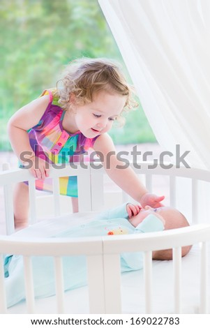 Adorable little toddler girl with curly hair playing with her newborn baby brother in a white round bed next to a big window with garden view - stock photo