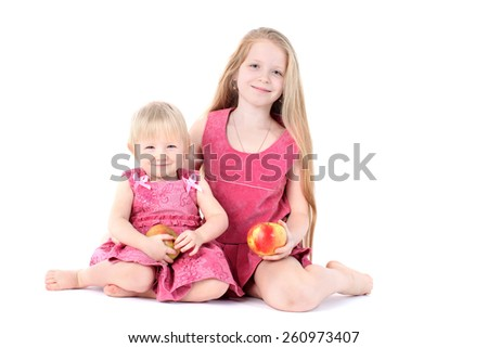 adorable little two sisters 9 year and  1  year old with apple on white background - stock photo