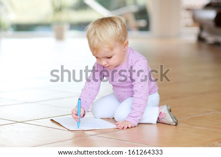 Adorable lovely baby girl plays indoors drawing with colorful pencils sitting on tiles floor - stock photo