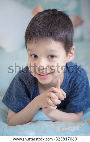 Adorable mixed race Asian Caucasian 5 year old boy lays in a cute pose on a bed inside his home - stock photo