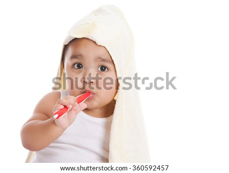 Adorable mixed race baby boy wearing a hooded towel and brushing his teeth.  Isolated on white.   - stock photo
