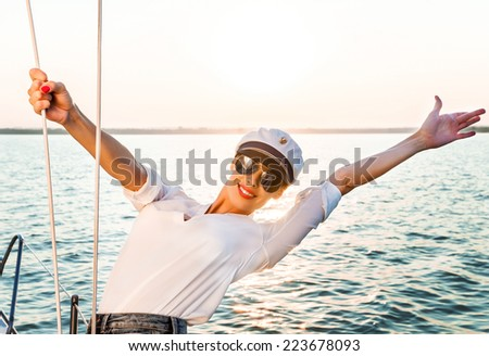 Adorable model wearing sea admirals hat and sexy top at sunset. - stock photo