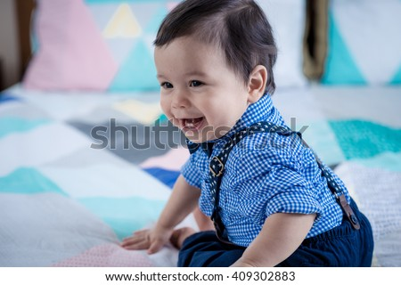 Adorable 11 month old mixed race Asian Caucasian boy dressed in braces and a bow tie plays cheerfully on a colorful geometrically shaped bed cover. Natural indoor lighting - stock photo