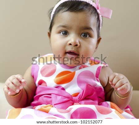 Adorable 6 months old Indian baby girl sitting on sofa - stock photo