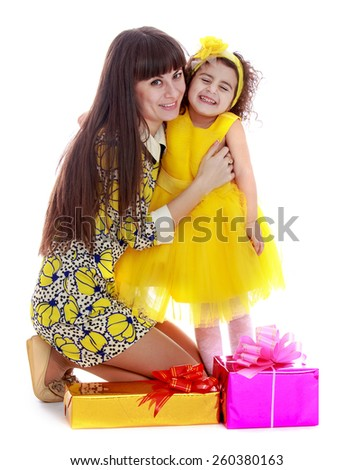 Adorable mother and daughter near Christmas gifts - isolated on white. - stock photo