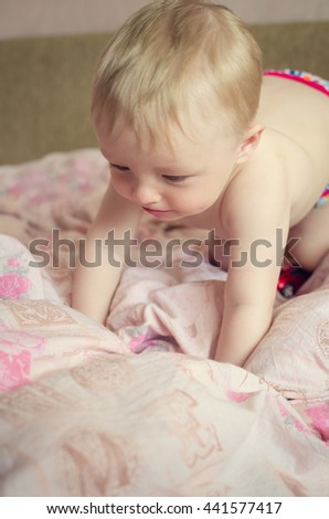 Adorable naked baby boy with big blue eyes lying on the bed. Cute toddler in pink diaper lying on his stomach on the pink sheet and looking aside. Beautiful baby is lying on a bed. - stock photo