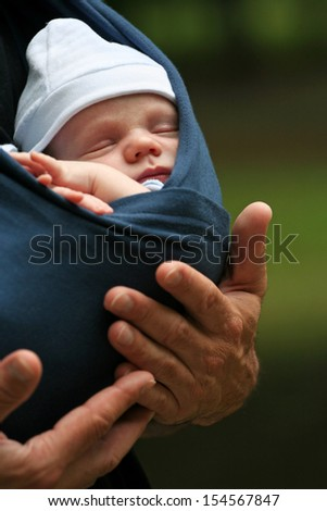 Adorable new-born baby boy sleeping in his daddy's hand - stock photo