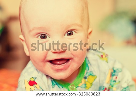 Adorable newborn baby boy laughing. Image with vintage filter - stock photo