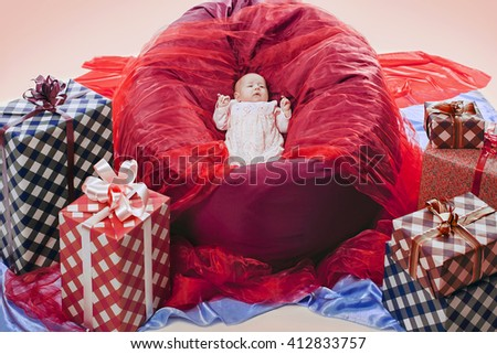 Adorable newborn baby girl lying in basket near present boxes - stock photo