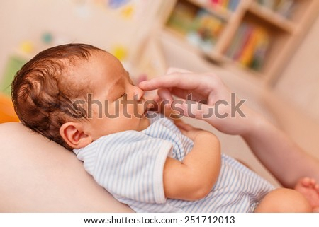Adorable newborn baby in the arms of my mother, close-up - stock photo