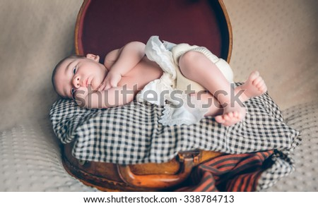 Adorable newborn baby resting lying over a plaid blanket on top of a vintage travel suitcase - stock photo