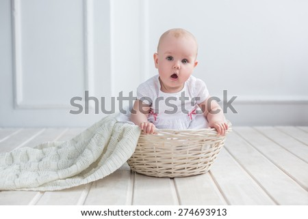 adorable nice baby portrait sitting in basket with blanket on white background  - stock photo