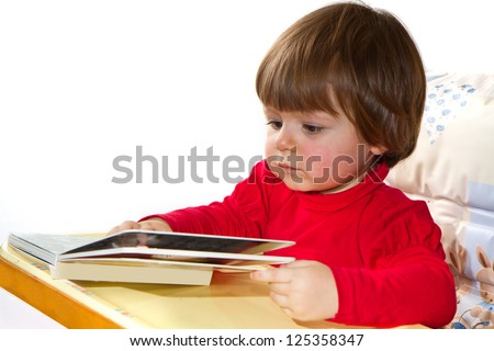 adorable one-year old baby reading a book - stock photo