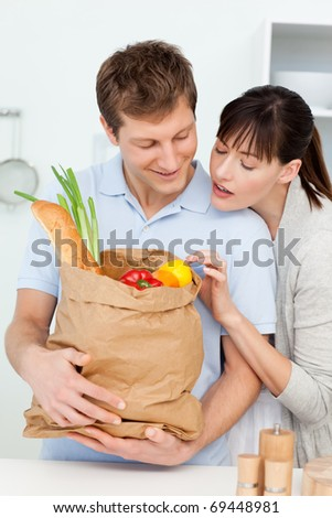 Adorable pairs looking at the shopping bags at home - stock photo