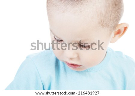 Adorable pensive  little boy at the age of two in a blue T-shirt on a white background - stock photo
