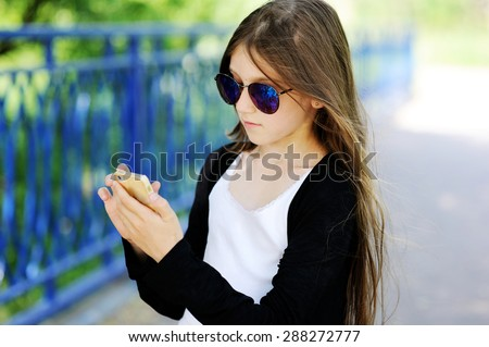 Adorable pre-teen tweenie kid girl in sunglasses making self portrait with funny  face on her  smartphone - stock photo
