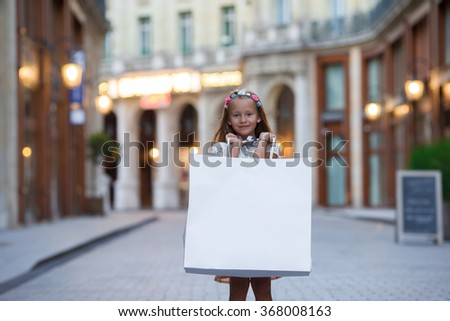 Adorable preschool girl walking with shopping bags in Paris outdoors - stock photo
