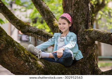 Adorable preschooler girl sitting on tree in the park - stock photo