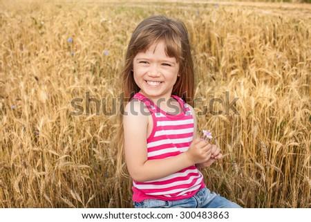 Adorable preschooler girl walking happily in wheat field on warm - stock photo