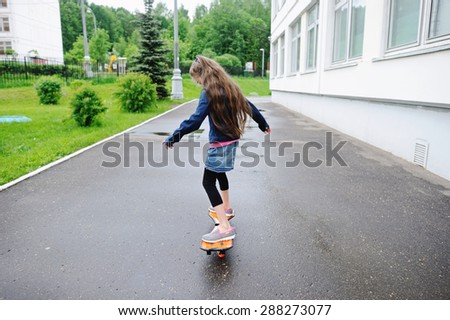 Adorable preteen tweem brunette girl  riding a skateboard in town - stock photo