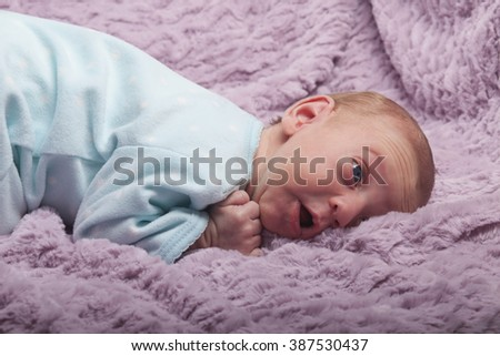 Adorable redhead newborn baby looks up with surprised expression - stock photo