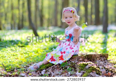 Adorable romantic child, blonde healthy toddler girl enjoying nature, playing and hiking in spring forest, picking, touching and holding snowdrops flowers - stock photo