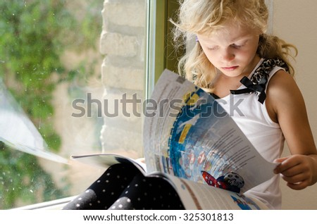 adorable scholar blond girl sitting by the window and reading book - stock photo