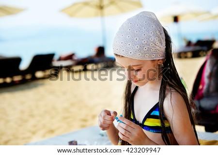 Adorable school aged  kid  girl having fun and handwork  on beach vacation  - stock photo