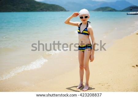 Adorable school aged  kid  girl having fun  on beach vacation  - stock photo