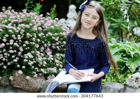 Adorable school aged kid girl in blue uniform dress outdoor  - stock photo