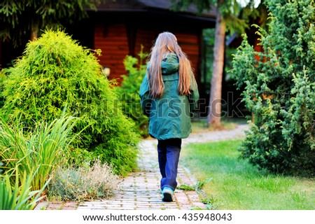 adorable school aged kid girl in colorful green warm jacket in the beauty fall park - stock photo