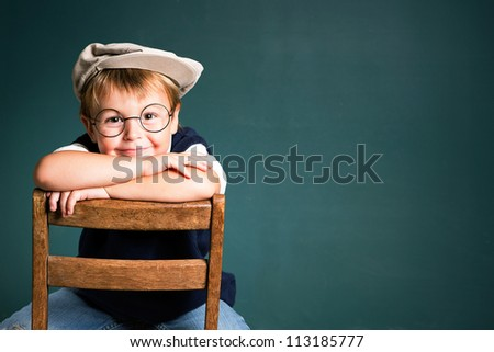 Adorable school boy with chalkboard copy space - stock photo