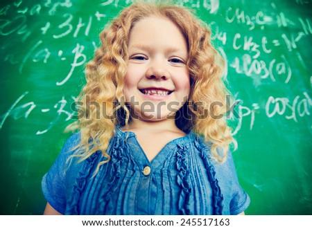 Adorable schoolgirl looking at camera on background of blackboard - stock photo