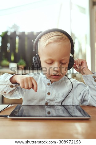 Adorable serious little boy choosing a soundtrack from his music library on a tablet as he sits at a table on an open-air patio wearing a set of stereo headphones on a sunny summer day - stock photo