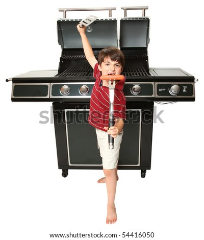 Adorable seven year old boy with grill utensils in front of large gas grill. - stock photo