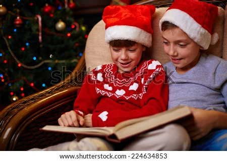 Adorable siblings in Santa caps reading book together on Christmas evening - stock photo