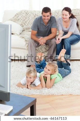 Adorable siblings watching television with their parents lying on the floor in the living-room - stock photo