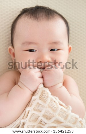 Adorable six months old teething Asian baby girl lying on bed biting blanket. - stock photo