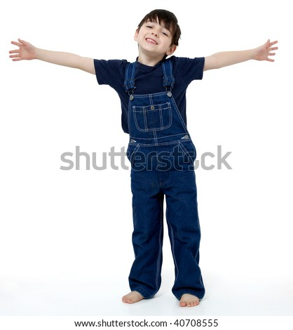Adorable six year old boy in overalls with his arms stretched out to show size or invite hug. - stock photo