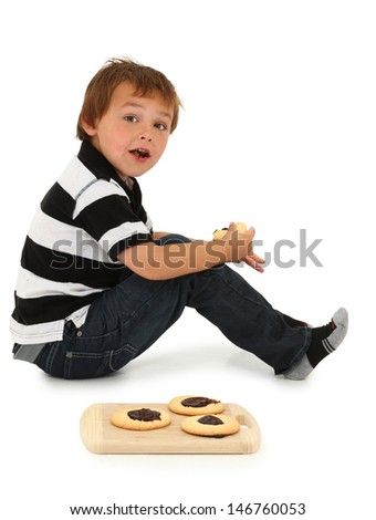 Adorable six year old Caucasian boy sitting on floor eating sugar cookies with chocolate center. - stock photo