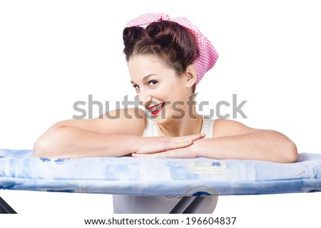 Adorable sixties pin up lady resting on ironing board wearing headscarf and old-fashioned hair style. On white background - stock photo