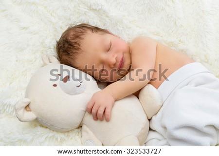 Adorable sleeping newborn baby boy hugging toy teddy bear - stock photo
