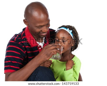 Adorable small african child with braids wearing a bright green shirt and blue jeans is with her father. He is wearing a red striped shirt and is helping her to drink water from a glass. - stock photo