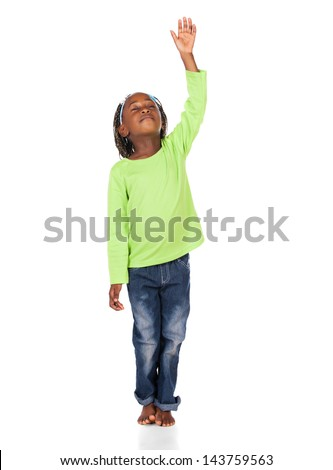 Adorable small african child with braids wearing a bright green shirt and blue jeans. The girl is worshipping with her hand lifted up. - stock photo
