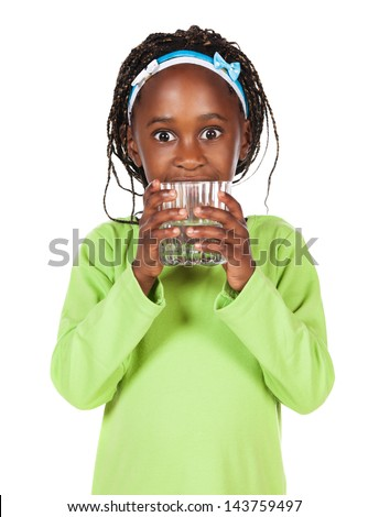 Adorable small african child with braids wearing a bright green shirt. The girl is holding a clear glass of water. - stock photo