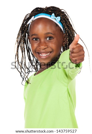 Adorable small african child with braids wearing a bright green shirt. The girl is showing a thumbs up to the camera. - stock photo