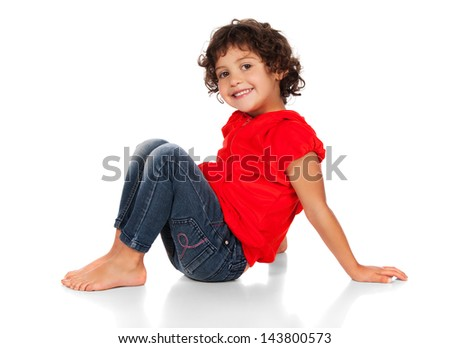 Adorable small caucasian child with curly hair wearing a bright red hooded top and blue jeans. The girl is sitting and smiling at the camera. - stock photo