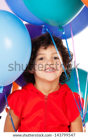 Adorable small caucasian child with curly hair wearing a bright red hooded top. The girl is holding a bunch of bright coloured helium balloons. - stock photo